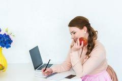 mooie vrouw die iets schrijven aan notitieboekje en appel houden royalty-vrije stock afbeelding