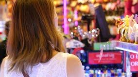 Mooie vrouw die juwelen op showcase bekijken Jonge dame die bijouterie in wandelgalerij genieten van 3840x2160 stock videobeelden