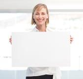 Mooie vrouw die lege witte raad houdt Stock Afbeeldingen