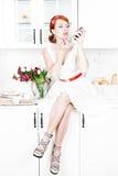 Mooie vrouw die lippenstift op de keuken toepassen Stock Afbeelding