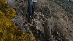 Mooie vrouw die in lopapeysasweater in de bergen dichtbij de Vatnajokull-ijsbergenlagune wandelen in IJsland stock video