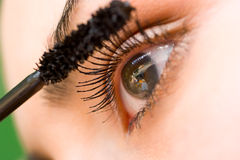 Mooie vrouw die mascara op haar oog toepast Royalty-vrije Stock Fotografie