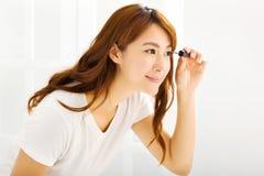 mooie vrouw die mascara in slaapkamer toepassen Stock Afbeelding