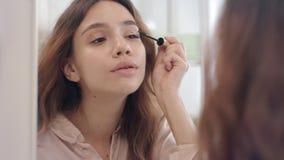 Mooie vrouw die mascara voor spiegel van de wimpers de voorbadkamers gebruiken stock video