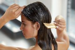 Mooie Vrouw die Masker op Lang Nat Haar zetten Hairbrushing stock foto's
