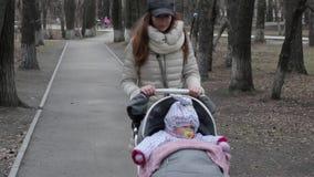 Mooie vrouw die met haar weinig dochter lopen en duwwandelwagen in park duwen Mammagangen met een wandelwagen in het park stock videobeelden