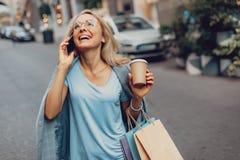 Mooie vrouw die met hete drank telefoon van gesprek en het lachen genieten stock afbeeldingen