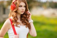 Mooie vrouw die met hoofdtelefoons aan muziek luistert Stock Foto