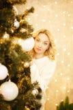 Mooie vrouw die met die Kerstmanhoed achter Kerstboom gluren, op witte achtergrond wordt geïsoleerd royalty-vrije stock fotografie
