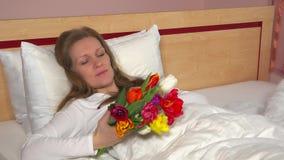 Mooie vrouw die met kleurrijke tulpenbloemen op het bed glimlachen stock footage