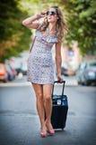 Mooie vrouw die met koffers de straat in een grote stad kruisen Stock Fotografie