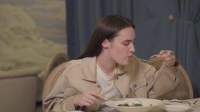 Mooie vrouw die met lang haar noedels met greens en plantaardige zitting eten bij de lijst in het restaurant Eenzame Dame stock footage