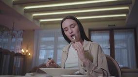Mooie vrouw die met lang haar shpimps prouns zitting eten bij de lijst in het restaurant Eenzame dame die van haar maaltijd genie stock video