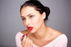 Mooie vrouw die met onberispelijke teint rode lipgloss toepassen royalty-vrije stock afbeelding