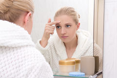 Mooie vrouw die met probleemhuid spiegel in badkamers bekijken Stock Foto's