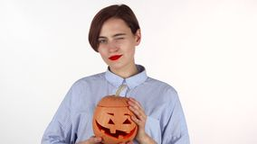 Mooie vrouw die met rode lippen, Halloween-pompoen houden gelukkig glimlachen die stock footage