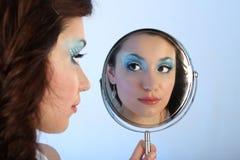 Mooie vrouw die met samenstelling spiegel bekijkt Stock Foto