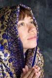 Mooie vrouw die met sjaal het bidden glimlacht Stock Fotografie