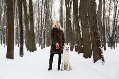 Mooie vrouw die met Witte Zwitserse herdershond lopen in de winter royalty-vrije stock foto