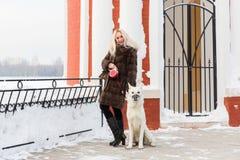 Mooie vrouw die met Witte Zwitserse herdershond lopen in de winter stock afbeeldingen