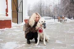 Mooie vrouw die met Witte Zwitserse herdershond lopen in de winter stock foto