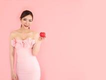 Mooie vrouw die minihart op hand, maniermeisje op roze houden Stock Afbeeldingen