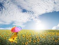 Mooie vrouw die multicolored paraplu in zonnebloemgebied en wolkenhemel houden Royalty-vrije Stock Foto