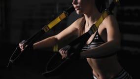 Mooie vrouw die oefening met trxriemen doen in donkere gymnastiek stock videobeelden