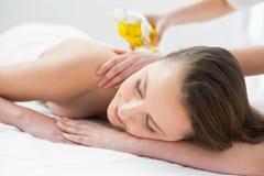 Mooie vrouw die olie van massage geniet in beauty spa Royalty-vrije Stock Afbeeldingen