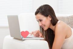 Mooie vrouw die online op laptop dateren Stock Foto's