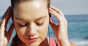 Mooie vrouw die oortelefoons in haar oor zetten vóór jogging stock videobeelden