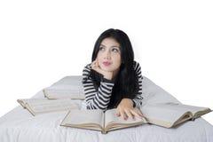 Mooie vrouw die op bed met boeken liggen Royalty-vrije Stock Afbeeldingen