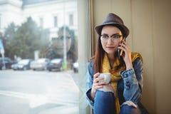 Mooie vrouw die op cellphone bij koffie spreken Stock Fotografie