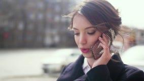Mooie vrouw die op cellphone door stadsstraat spreken stock videobeelden