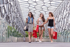 3 mooie vrouw die op de brug lopen, die van het winkelen genieten Stock Foto's