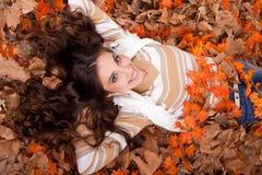 Mooie vrouw die op de herfstbladeren ligt Royalty-vrije Stock Foto