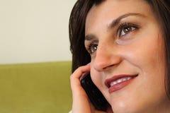 Mooie vrouw die op de telefoon spreekt en smil Stock Fotografie