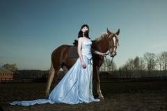 Mooie vrouw die op een bruin paard berijdt Stock Afbeelding