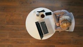 Mooie vrouw die op glas zetten en aan haar laptop aan een modieus stedelijk restaurant werken royalty-vrije stock foto's