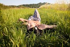 Mooie vrouw die op gras leggen stock foto's