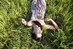 Mooie vrouw die op gras leggen royalty-vrije stock foto's
