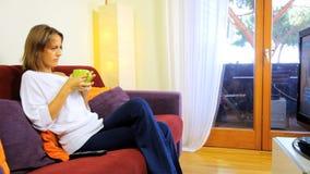 Mooie vrouw die op het gelukkige ontspannen van TV letten stock videobeelden