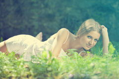 Mooie Vrouw die op het gras, rust in aard ligt Stock Fotografie