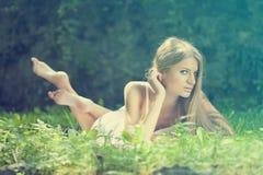 Mooie Vrouw die op het gras, rust in aard ligt Royalty-vrije Stock Afbeelding