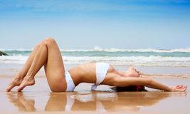 Mooie vrouw die op het natte zand ligt Stock Foto's