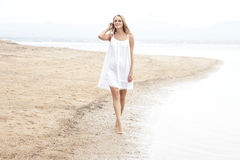 Mooie vrouw die op het strand lopen die van de zomer genieten Stock Foto's