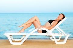 Mooie vrouw die op het strand zonnebaadt Royalty-vrije Stock Fotografie