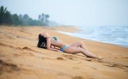 Mooie vrouw die op het zand op het strand in de zomer liggen Het geluk onbezorgde blije vrouw van de de zomervakantie stock fotografie