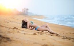 Mooie vrouw die op het zand op het strand in de zomer liggen Het geluk onbezorgde blije vrouw van de de zomervakantie stock afbeeldingen