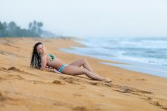Mooie vrouw die op het zand op het strand in de zomer liggen Het geluk onbezorgde blije vrouw van de de zomervakantie royalty-vrije stock foto's